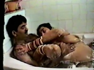 Really hairy Indian guy cuddling in the bathtub with his busty wife