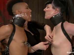 Two cruel mistresses are torturing an ebony slave